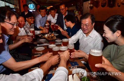 President Moon Jae-in (second from R) makes a toast while attending a meeting with citizens at a local pub in downtown Seoul on July 26, 2018, in a rare move to directly listen to the people's opinions about current issues that included the proposed minimum wage hike. (Yonhap)