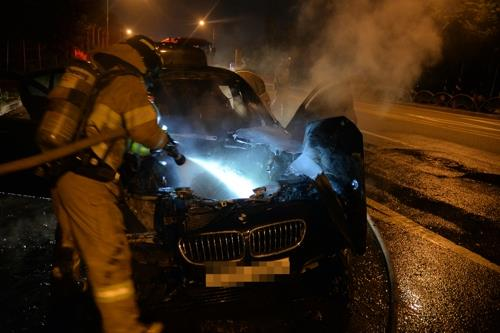 Firefighters put out a fire in a BMW 520d sedan on a road in Hanam, east of Seoul, on Aug. 12, 2018, in this photo provided by the Hanam Fire Station. (Yonhap)