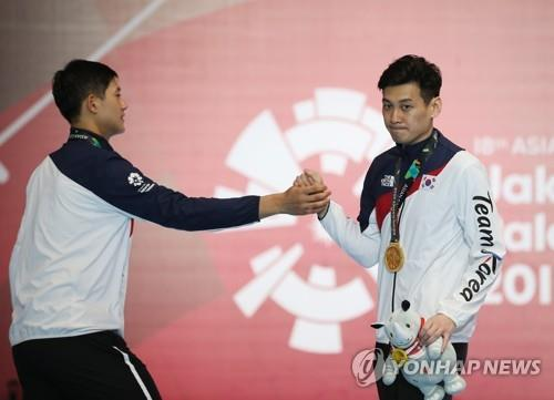 South Korean sabre fencer Gu Bon-gil (R) is congratulated by his teammate Oh Sang-uk during the medal ceremony of the men's individual sabre event at the 18th Asian Games at Jakarta Convention Center (JCC) Cendrawasih Hall in Jakarta on Aug. 20, 2018. Gu defeated Oh 15-14 in the final. (Yonhap)