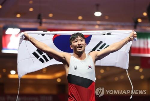 South Korean Greco-Roman wrestler Ryu Han-su celebrates his gold medal in the men's 67kg division at the 18th Asian Games at Jakarta Convention Center Assembly Hall in Jakarta on Aug. 21, 2018. (Yonhap)