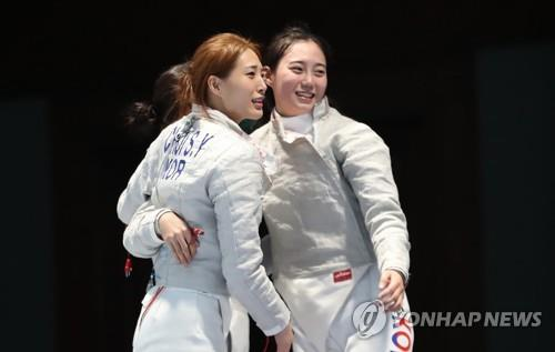 South Korean sabre fencers Choi Soo-yeon (L) and Yoon Ji-su celebrate their women's team gold medal over China at the 18th Asian Games at Jakarta Convention Center (JCC) Cendrawasih Hall in Jakarta on Aug. 22, 2018. (Yonhap)