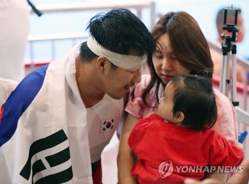 South Korean Greco-Roman wrestler Cho Hyo-chul enjoys a tender moment with his wife Kim Young-jin and daughter Seo-yoon after winning gold medal in the men's 97kg class at the 18th Asian Games in Jakarta on Aug. 22, 2018. (Yonhap)