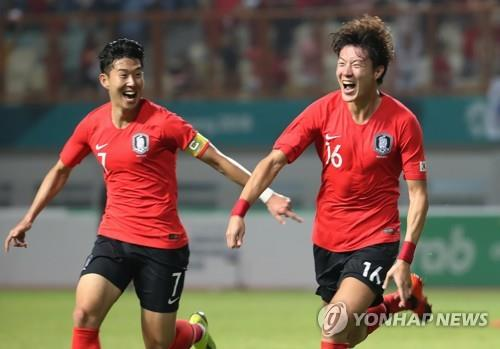 South Korea's Hwang Ui-jo (R) celebrates his goal with Son Heung-min during the men's football round of 16 match against Iran at the 18th Asian Games at Wibawa Mutkit Stadium in Chikarang, Indonesia, on Aug. 23, 2018. (Yonhap)