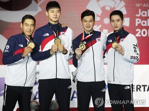 Members of the South Korean men's sabre fencing team hold their gold medals after defeating Iran at the 18th Asian Games Jakarta Convention Center (JCC) Cendrawasih Hall in Jakarta on Aug. 23, 2018. From left: Kim Jung-hwan, Oh Sang-uk, Gu Bon-gil and Kim Jun-ho. (Yonhap)