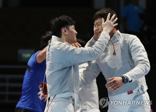 South Korean sabre fencer Gu Bon-gil (L) embraces teammate Oh Sang-uk after clinching the men's team gold medal at the 18th Asian Games Jakarta Convention Center (JCC) Cendrawasih Hall in Jakarta on Aug. 23, 2018. (Yonhap)