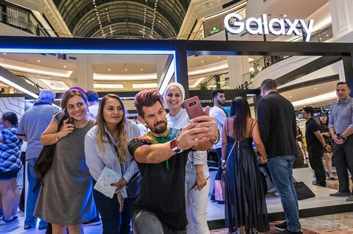 Models take a selfie with Samsung Electronics Co.'s Galaxy Note 9 smartphone at a booth located in Dubai, the United Arab Emirates, in this photo released by the company on Aug. 24, 2018. (Yonhap)