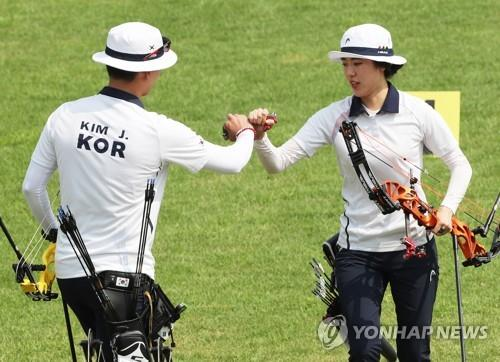 South Korean compound archers Kim Jong-ho (L) and So Chae-won bump fists during the mixed team final against Chinese Taipei at the 18th Asian Games at GBK Archery Field in Jakarta on Aug. 27, 2018. (Yonhap)