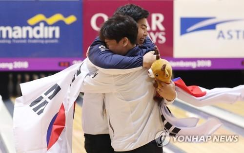 South Korean bowlers Park Jong-woo (L) and Koo Seong-hoi embrace after winning silver and bronze medals in the men's Masters event at the 18th Asian Games at Jakabaring Sports City Bowling Center in Palembang, Indonesia, on Aug. 27, 2018. (Yonhap)