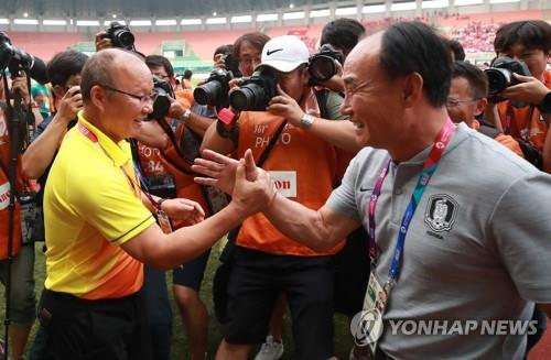 Park Hang-seo (L), head coach of Vietnam U-23 football team, shakes hands with South Korea U-23 football head coach Kim Hak-bum ahead of the men's football semifinal match at the 18th Asian Games at Pakansari Stadium in Cibinong, south of Jakarta, on Aug. 29, 2018. (Yonhap)