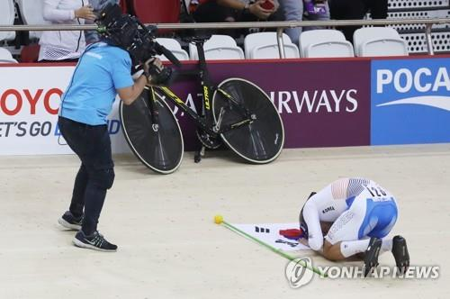 South Korean track cyclist Park Sang-hoon takes a kneeling bow to his bicycle after winning gold in the men's individual pursuit race at the 18th Asian Games at Jakarta International Velodrome in Jakarta on Aug. 29, 2018. (Yonhap)