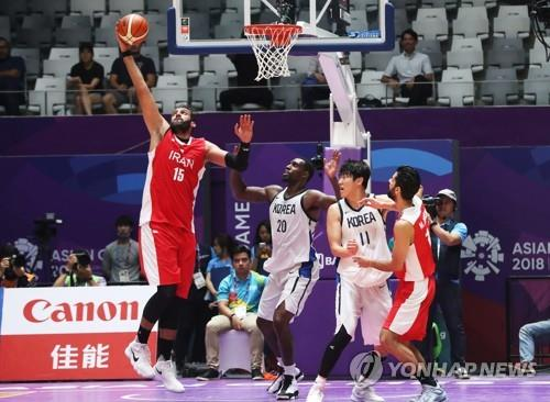 Hamed Haddadi (R) of Iran catches a rebound during the men's basketball semifinal match between South Korea and Iran at the 18th Asian Games in Jakarta on Aug. 30, 2018. (Yonhap)