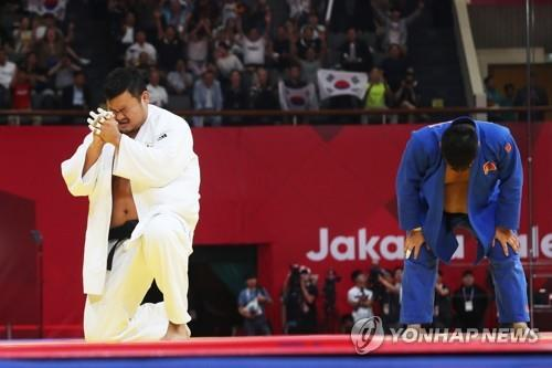 South Korean judoka Kim Sung-min (L) celebrates after winning the men's over-100 kilogram division final at the 18th Asian Games at Jakarta Convention Center Plenary Hall in Jakarta on Aug. 31, 2018. (Yonhap)