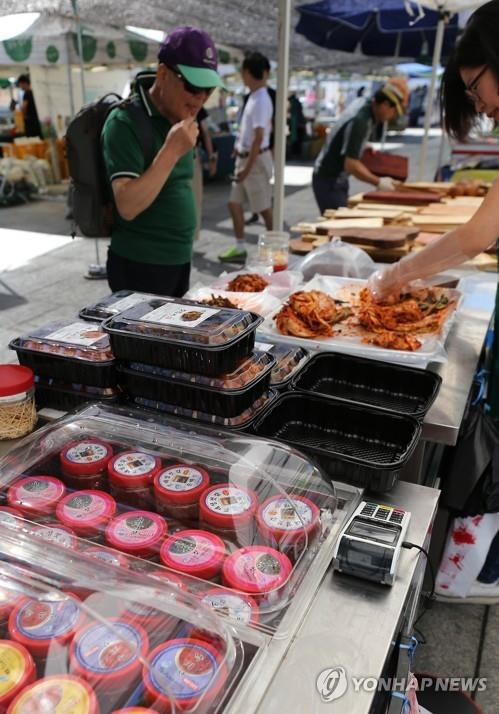 A visitor tastes kimchi at a farmer's market in Gwanghwamun Square in downtown Seoul on Sept. 2, 2018. (Yonhap)