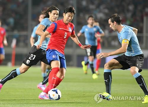 This file photo taken Sept. 8, 2014, shows South Korea's Son Heung-min (C) dribbling against Uruguay's Diego Godin (R) and Edinson Cavani during a friendly football match between South Korea and Uruguay at Goyang Stadium in Goyang, north of Seoul. (Yonhap)