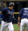 In this Getty Images photo, Choi Ji-man of the Tampa Bay Rays (L) is congratulated by his third base coach Matt Quatraro after hitting a two-run home run against the Cleveland Indians in the bottom of the first inning of a Major League Baseball regular season game at Tropicana Field in St. Petersburg, Florida, on Sept. 12, 2018. (Yonhap)