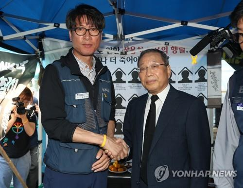 SsangYong Motor Co. CEO Choi Jong-sik (R) shakes hands with Kim Deuk-joong, the manager of the Korean Metal Workers' Union's SsangYong Motor branch, at a temporary memorial altar for late SsangYong Motor workers in Seoul on Sept. 13, 2018. (Yonhap)