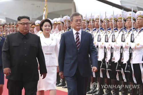 South Korean President Moon Jae-in (R) and North Korea's top leader, Kim Jong-un, review an honor guard at a welcoming ceremony for Moon at Pyongyang International Airport on Sept. 18, 2018. Moon arrived on the day for a three-day visit to North Korea for his third summit with Kim. (Pool photo) (Yonhap)