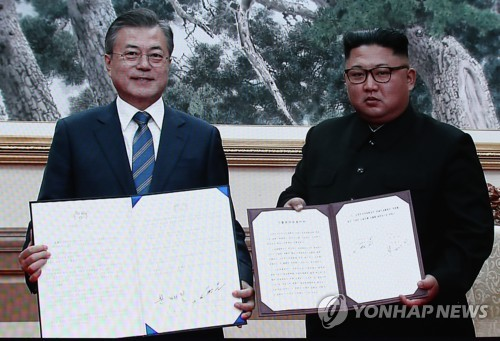 The captured image of a live broadcast from Pyongyang shows South Korean President Moon Jae-in (L) and North Korean leader Kim Jong-un holding their joint declaration signed at the end of their bilateral summit held in the North Korean capital on Sept. 19, 2018. (Yonhap)