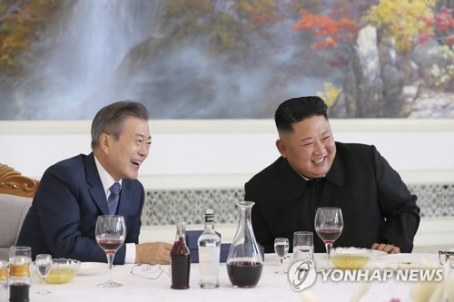 South Korean President Moon Jae-in (L) and North Korean leader Kim Jong-un laugh while having lunch at a Pyongyang restaurant on Sept. 19, 2018, the second day of Moon's three-day trip to the North Korean capital for his third bilateral summit with Kim. (Yonhap)
