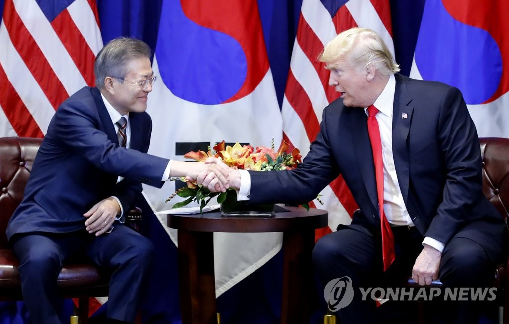 South Korean President Moon Jae-in (L) and U.S. President Donald Trump shake hands after meeting in New York for a bilateral summit on Sept. 24, 2018. (Yonhap)