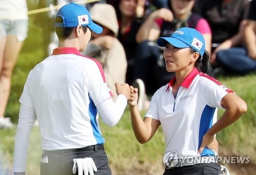 Park Sung-hyun (L) and Kim In-kyung of South Korea bump fists after Park's eagle at the 14th hole during the UL International Crown at Jack Nicklaus Golf Club Korea in Incheon, 40 kilometers west of Seoul. (Yonhap)