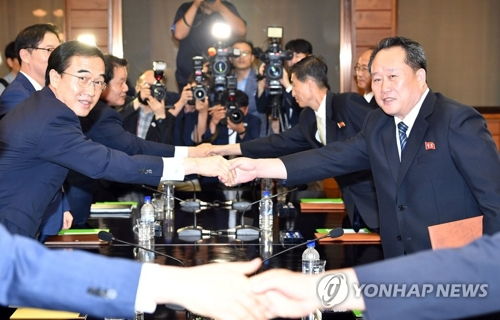 South Korean Unification Minister Cho Myoung-gyon (L) shakes hands with Ri Son-gwon, a senior North Korean official, in their talks at Panmunjom on Aug. 13, 2018. (Joint press corps-Yonhap)