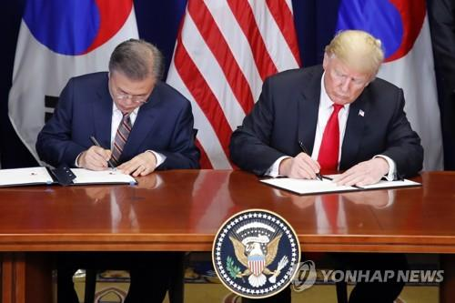 South Korean President Moon Jae-in (L) and U.S. President Donald Trump sign the official document on the revised free trade agreement between the two allies at Lotte New York Palace in New York on Sept. 24, 2018. (Yonhap)