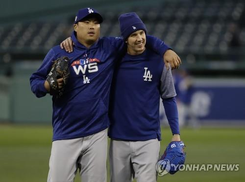 In this Associated Press photo, Ryu Hyun-jin (L) and Walker Buehler of the Los Angeles Dodgers put their arms around each other during practice ahead of Game 1 of the World Series at Fenway Park in Boston on Oct. 22, 2018. (Yonhap)