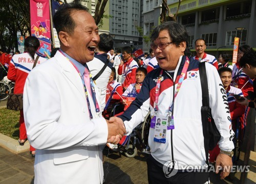 This pool photo, taken Oct. 4, 2018, shows the North Korean delegation's chef de mission, Jong Hyon (L), shaking hands with South Korea's chef de mission, Jun Min-sik, during a welcome ceremony at the athletes' village in Jakarta for the 3rd Asian Para Games. (Yonhap)