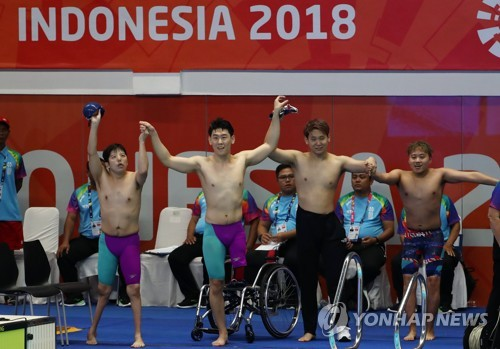 The unified Korean para swimming team athletes celebrate after finishing their 400-meter freestyle relay event at the 3rd Asian Para Games at Gelora Bung Karno Aquatic Center in Jakarta on Oct. 8, 2018. (Yonhap)