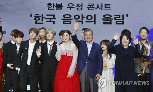 South Korean President Moon Jae-in (fourth from left) waves to a French audience in a cultural event held in Paris on Oct. 14, 2018 to mark his state visit to France. The special event included performances by famous South Korean boy group BTS. (Yonhap)