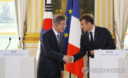 South Korean President Moon Jae-in (L) and French President Emmanuel Macron shake hands after holding a joint press conference to explain the outcome of their bilateral summit held at the Elysee Palace in Paris on Oct. 15, 2018. (Yonhap)