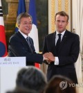 South Korean President Moon Jae-in (L) and French President Emmanuel Macron clasp hands after holding a joint press conference to announce the outcome of their bilateral summit at the Elysee Palace in Paris on Oct. 15, 2018. (Yonhap)