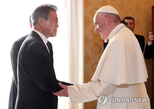 South Korean President Moon Jae-in (L) holds hands with Pope Francis while paying a courtesy call on the pontiff in the Vatican on Oct. 18, 2018. (Yonhap)