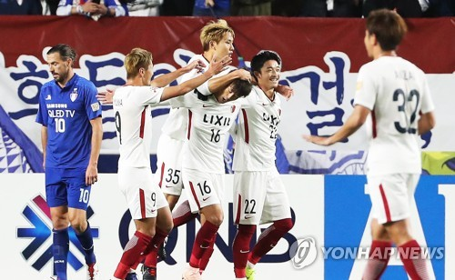 Kashima Antlers players celebrate a goal as Suwon Samsung Bluewings forward Dejan Damjanovic (L) reacts during the second leg of their Asian Football Confederation Champions League (ACL) semifinal match at Suwon World Cup Stadium in Suwon, south of Seoul, on Oct. 24, 2018. (Yonhap)
