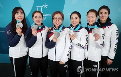 This file photo from Feb. 25, 2018, shows the South Korean women's curling team posing for a group photo after winning the silver medal at the 2018 PyeongChang Olympics. From left are Kim Cho-hee, Kim Yeong-mi, Kim Seon-yeong, Kim Kyeong-ae, skip Kim Eun-jung and head coach Kim Min-jung. (Yonhap)