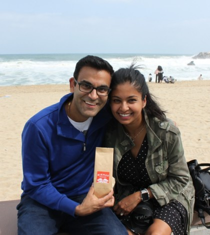 Neil Vasdev and his wife, Smita Jabob, pose for a photo with a bag of roasted coffee beans they purchased at a cafe along Anmok Beach in Gangneung, Gangwon Province. (Yonhap)
