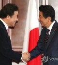 This photo, taken on Sept. 11, 2018, shows South Korean Prime Minister Lee Nak-yon (L) shaking hands with Japanese Prime Minister Shinzo Abe during a meeting on the sidelines of the 4th Eastern Economic Forum in Vladivostok, Russia. (Yonhap)