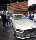 Genesis executives, from left, Erwin Raphael, Luc Donckerwolke, William Lee, and Mark Del Rosso pose for pictures with the G90 at the AutoMobility LA auto show Wednesday, Nov. 20, 2019, in Los Angeles. (AP Photo/Marcio Jose Sanchez)